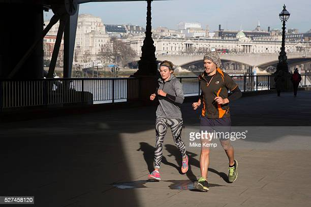 Lunchtime joggers run past through winter light on the riverfront walkway The South Bank is a significant arts and entertainment district and home to...
