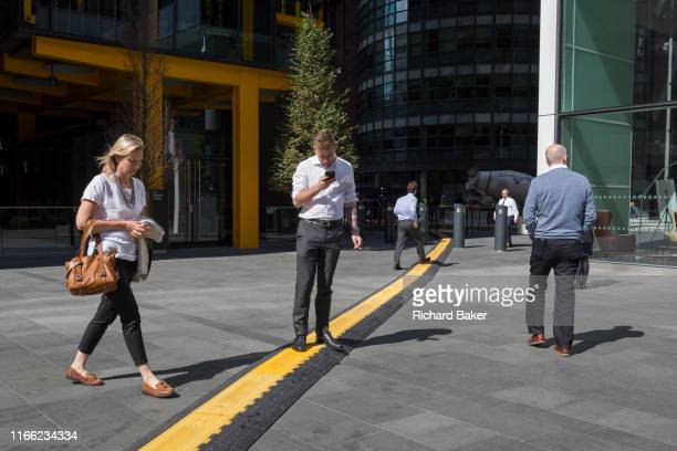 A lunchtime office worker crosses a yellow line covering hazardous electrical cabling at Leadenhall in the City of London the capital's financial...