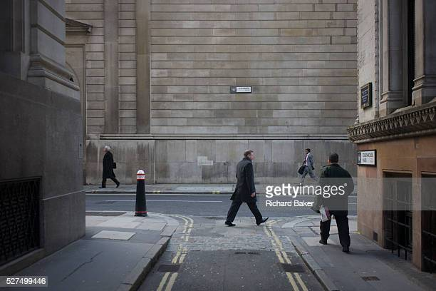 Lunchtime pedestrians on the corner of Lothbury and Tokenhouse Yard two narrow and historic streets with the high walls of the Bank of England in the...