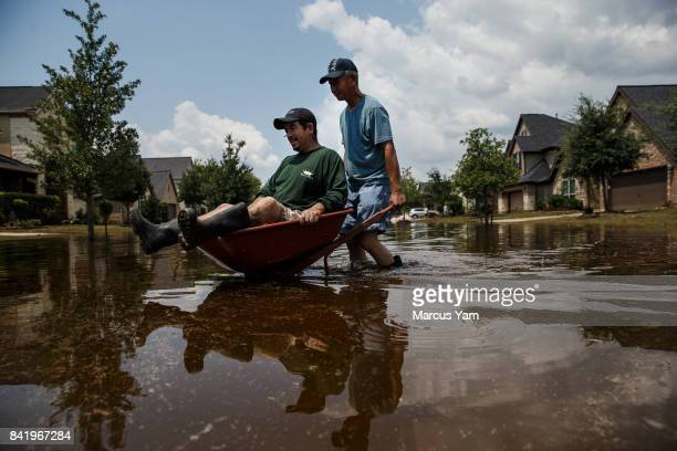 Lung Hui Chen pushes Manuel Terrazas in a wheel barrel across flooded streets as local residents clear out homes damaged in the aftermath of tropical...