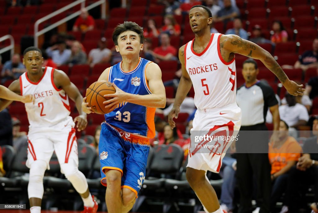 Luo Hanchen #33 of Shanghai Sharks drives to the basket defended by Troy Williams #5 of Houston Rockets in the fourth quarter at Toyota Center on October 5, 2017 in Houston, Texas.