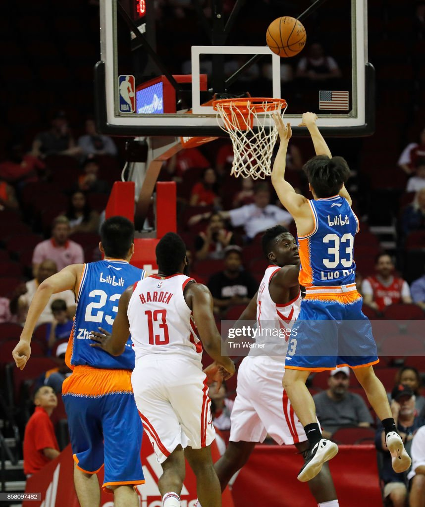 Luo Hanchen #33 of Shanghai Sharks takes a shot defended by Clint Capela #15 of Houston Rockets in the first half at Toyota Center on October 5, 2017 in Houston, Texas.