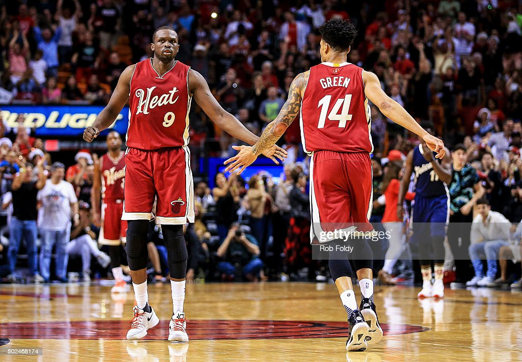 Luol Deng #9 and Gerald Green #14 of the Miami Heat slap hands during the game against the New Orleans Pelicans at American Airlines Arena on December 25, 2015 in Miami, Florida.