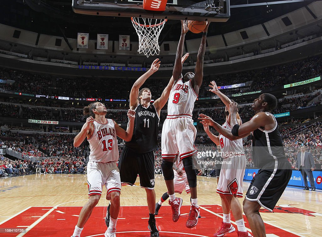 Luol Deng #9 of the Chicago Bulls goes to the basket against Brook Lopez #11 of the Brooklyn Nets on December 15, 2012 at the United Center in Chicago, Illinois.