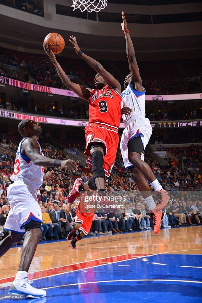 Luol Deng #9 of the Chicago Bulls goes to the basket against Jrue Holiday #11 of the Philadelphia 76ers at the Wells Fargo Center on December 12, 2012 in Philadelphia, Pennsylvania.