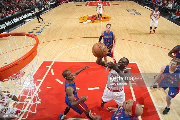 Luol Deng of the Chicago Bulls goes to the basket over Kim English and Charlie Villanueva of the Detroit Pistons on March 31 2013 at the United...
