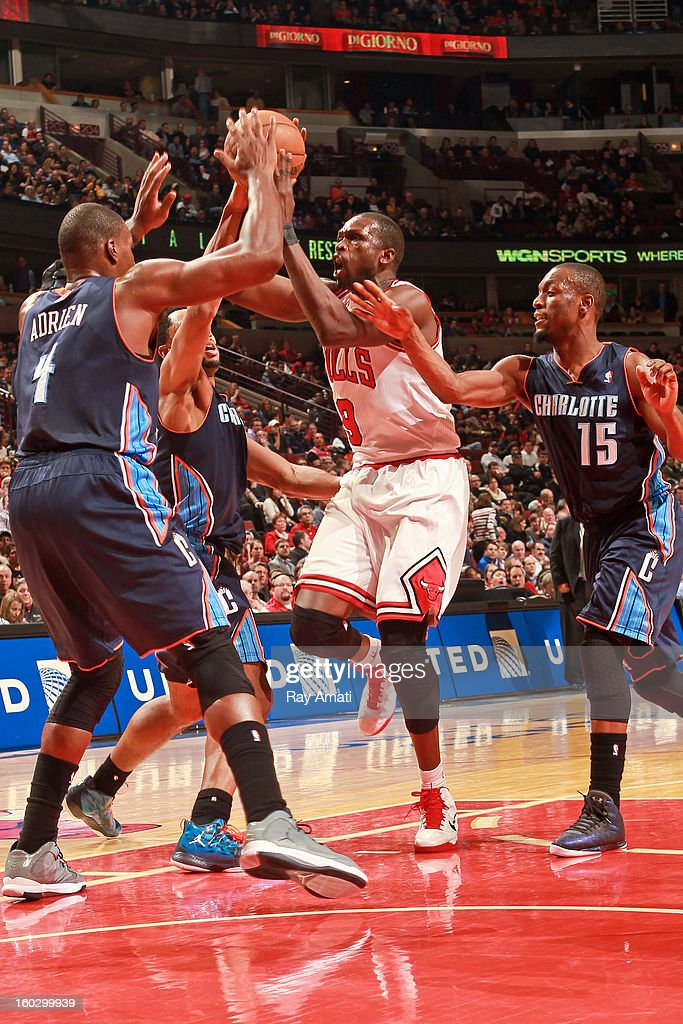 Luol Deng #9 of the Chicago Bulls looks to pass the ball against Jeff Adrien #4, Gerald Henderson #9 and Kemba Walker #15 of the Charlotte Bobcats on January 28, 2013 at the United Center in Chicago, Illinois.