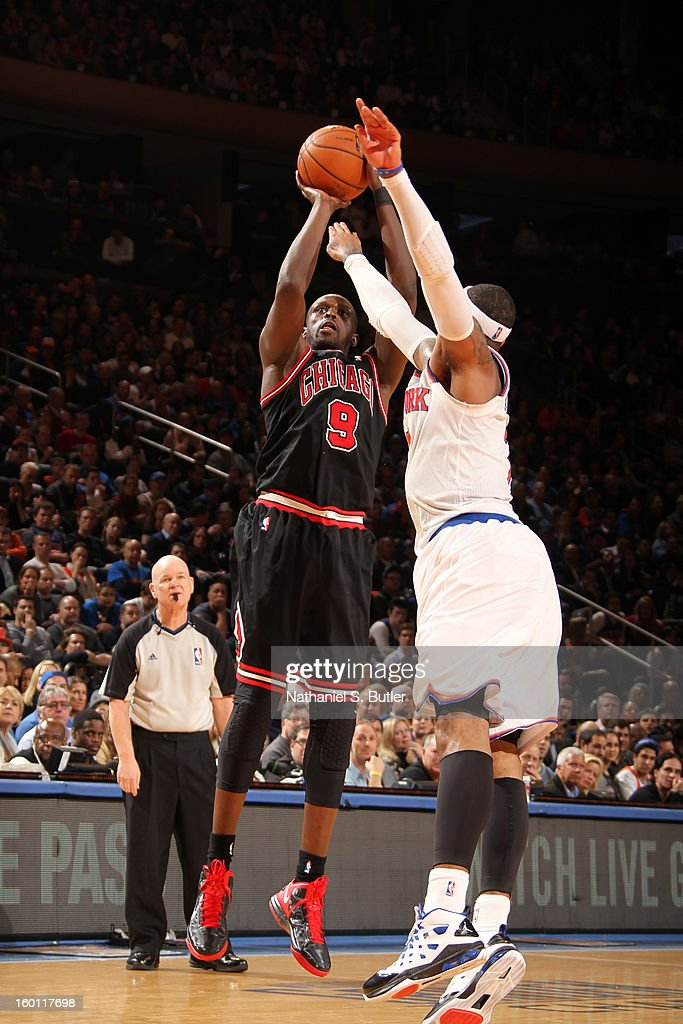 Luol Deng #9 of the Chicago Bulls shoots the ball against Carmelo Anthony #7 of the New York Knicks on January 11, 2013 at Madison Square Garden in New York City.