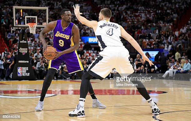 Luol Deng of the Los Angeles Lakers passes around Josh McRoberts of the Miami Heat during a game at American Airlines Arena on December 22 2016 in...