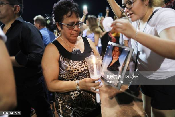 Lupe Lopez carries a photo Elsa Mendoza Marquez a Mexican schoolteacher from Ciudad Juarez who was killed in the shooting during an interfaith vigil...