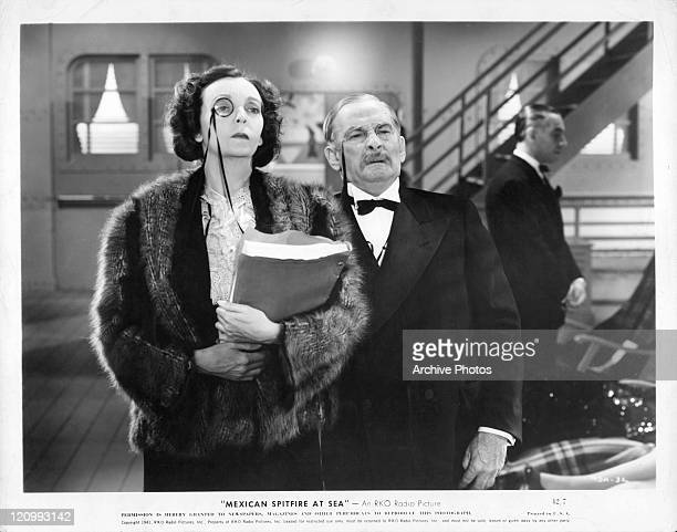 Lupe Velez holds manuscript standing next to male actor in a scene from the film 'Mexican Spitfire At Sea' 1942