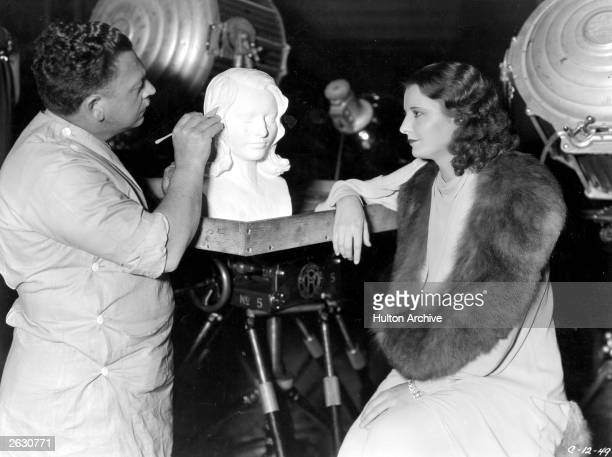 Lupe Velez the Mexican film actress posing for a bust that is being sculpted of her