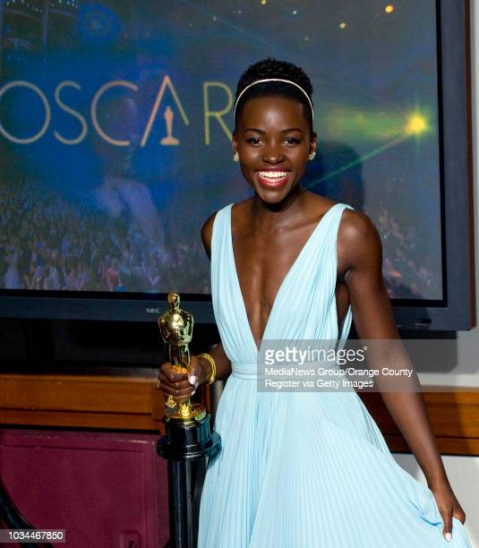 Lupita Nyong'o holds the Oscar after winning the Best Actress in a Supporting role for '12 Years a Slave' during the 86th annual Academy Awards at...