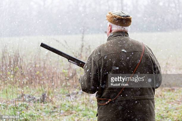 lurking hunter with a rifle, heavy snowing - czech hunters stock pictures, royalty-free photos & images