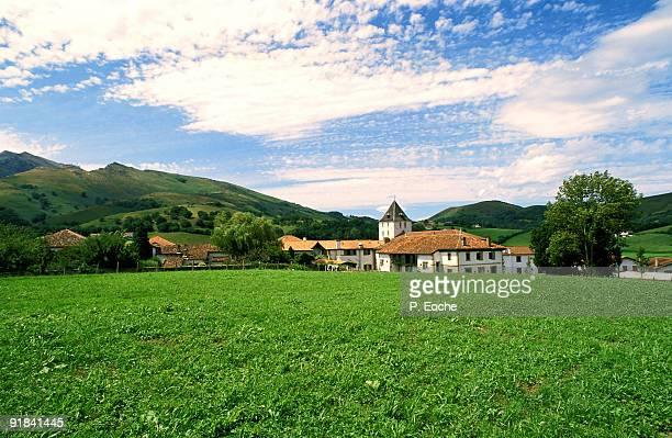 lush field by village, aquitaine, france. village de sare - pyrenees atlantique stock pictures, royalty-free photos & images