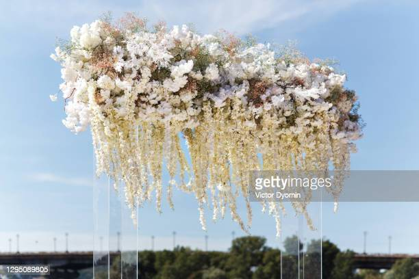 lush floral garland at the outdoor wedding reception - trouwceremonie stockfoto's en -beelden