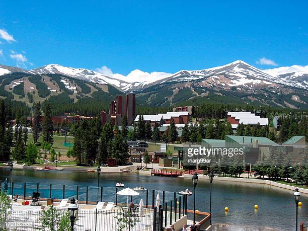 Lush summer resort facing snowy mountains in the distance