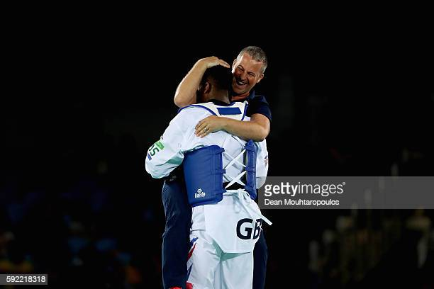 Lutalo Muhammad of Great Britain or Team GB celebrates with his coach after victory against Milad Beigi Harchegani of Azerbaijan during their Men's...