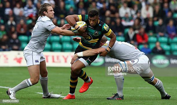 Luther Burrell of Northampton charges upfield as David Denton and Max Clark tackle during the Aviva Premiership match between Northampton Saints and...