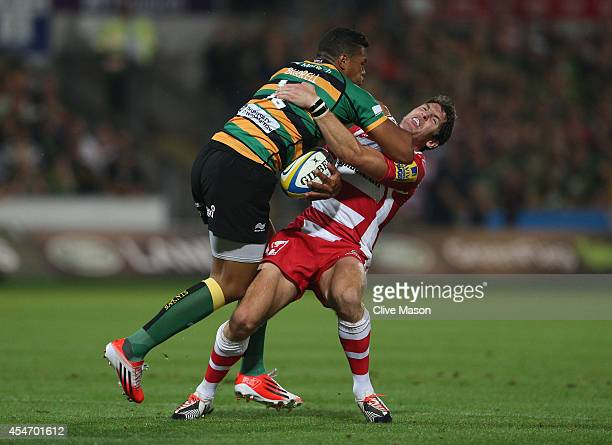 Luther Burrell of Northampton drives through James Hook of Gloucester during the Aviva Premiership match between Northampton Saints and Gloucester...