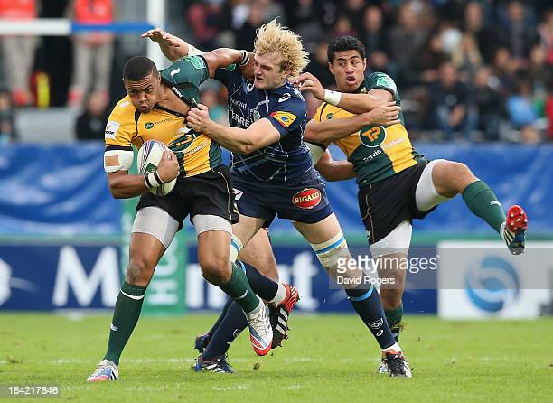 Luther Burrell of Northampton is tackled by Richie Gray during the Heineken Cup match between Castres and Northampton Saints at Stade Pierre Antoine...