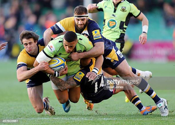 Luther Burrell of Northampton Saints is tackled by Ignacio Mieres, Sam Betty and James Stephenson of Worcester Warriors during the Aviva Premiership...