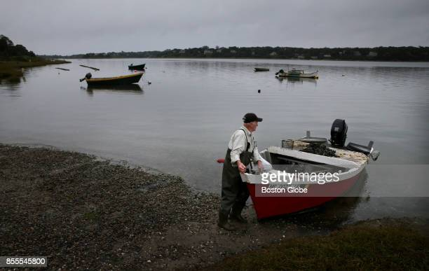 Luther Eldredge of Eastham works on his wooden flat bottom skiff while cleaning muscles at Collins Landing in Eastham MA on Sep 28 2017 He said he...