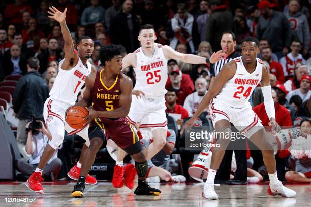 Luther Muhammad Andre Wesson and Kyle Young of the Ohio State Buckeyes defend against Marcus Carr of the Minnesota Golden Gophers in the first half...