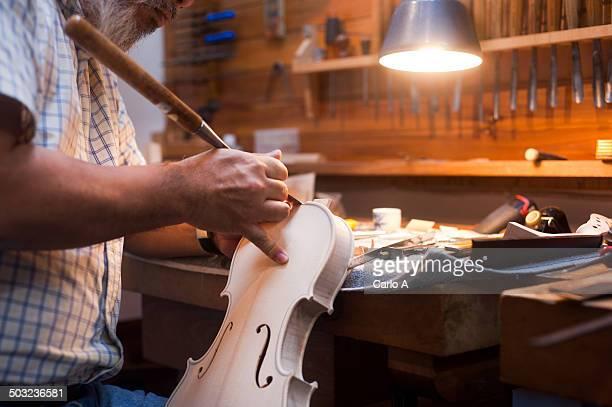 Luthier carving violin