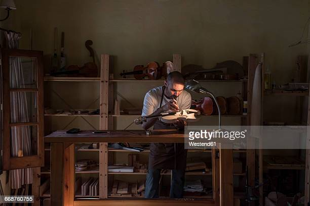 luthier examining the sound post of an unvarnished violin in his workshop - instrument maker stock photos and pictures
