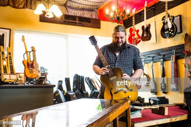 luthier in his guitar repair shop - instrument maker stock photos and pictures