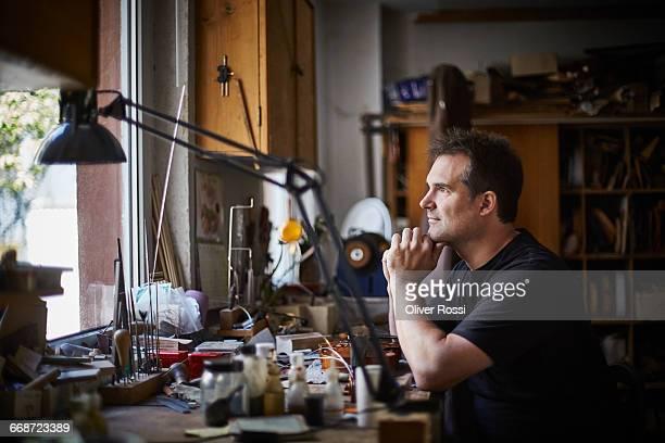 Luthier in workshop contemplating