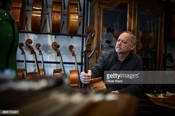 Luthier in workshop holding instrument