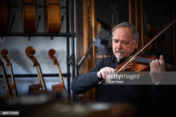 Luthier in workshop playing violin