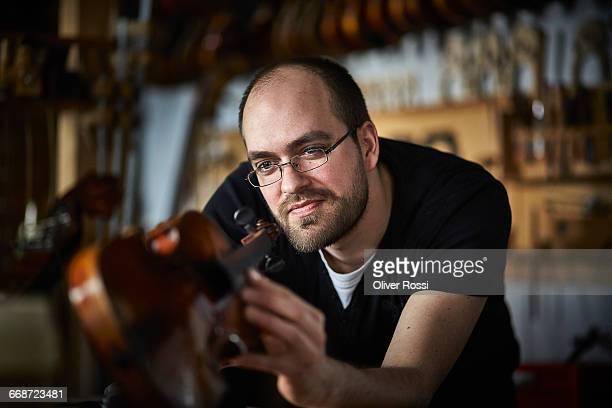Luthier in workshop scrutinizing violin