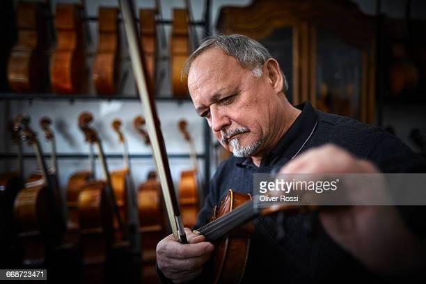 Luthier in workshop tuning violin