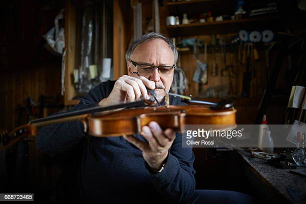luthier in workshop working on violin - instrument maker stock photos and pictures