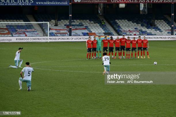 Luton FC players link arms before the game as Bournemouth players choose to 'take the knee' before the Sky Bet Championship match between Luton Town...