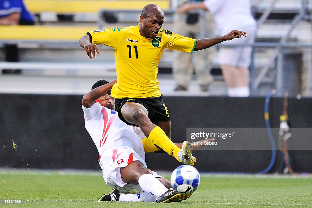 Luton Shelton #11 of Jamaica is tackled by Dario Delgado #2 of Costa Rica at Crew Stadium on July 7, 2009 in Columbus, Ohio.
