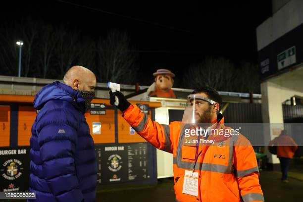 Luton Town fan has their temperature taken whilst wearing a face mask ahead of the Sky Bet Championship match between Luton Town and Norwich City at...