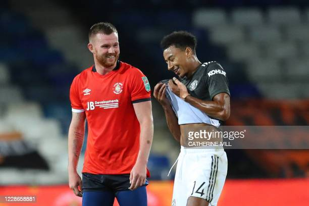 Luton Town's English midfielder Ryan Tunnicliffe and Manchester United's English midfielder Jesse Lingard react at the final whistle during the...