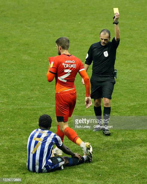 Luton Town's Martin Cranie is shown a yellow card by referee Geoff Eltringham for his foul on Sheffield Wednesday's Kadeem Harris during the Sky Bet...