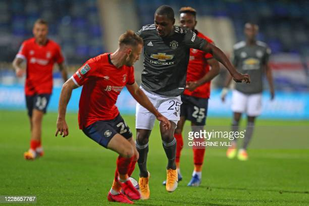 Luton Town's Welsh defender Rhys Norrington-Davies vies with Manchester United's Nigerian striker Odion Ighalo during the English League Cup third...