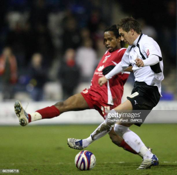 Luton's Darren Currie and Swindon's Miguel Comminges compete for the ball