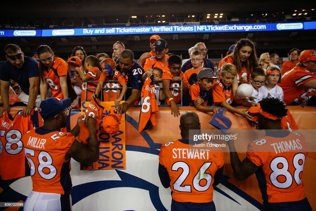 Lutside Linebacker Von Miller #58 of the Denver Broncos, Darian Stewart #26 and Demaryius Thomas #88 sign autographs for fans during a Preseason game against the Green Bay Packers at Sports Authority Field at Mile High on August 26, 2017 in Denver, Colorado. The Broncos defeated the Packers 20-17.