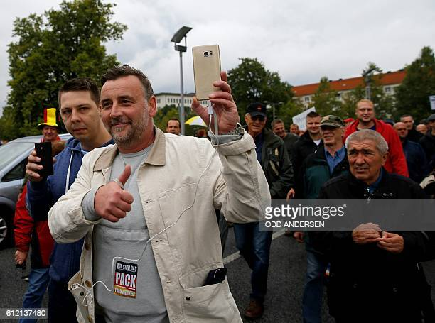 Lutz Bachmann cofounder of the Pegida movement documents with his mobile phone as he takes part in a protest against German Chancellor Angela Merkel...