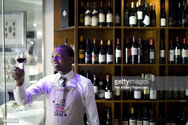 Luvo Ntezo a wine sommelier at the Twelve Apostles Hotel stands with a glass of red wine in a wine cellar on March 23 2010 in Cape Town South Africa...