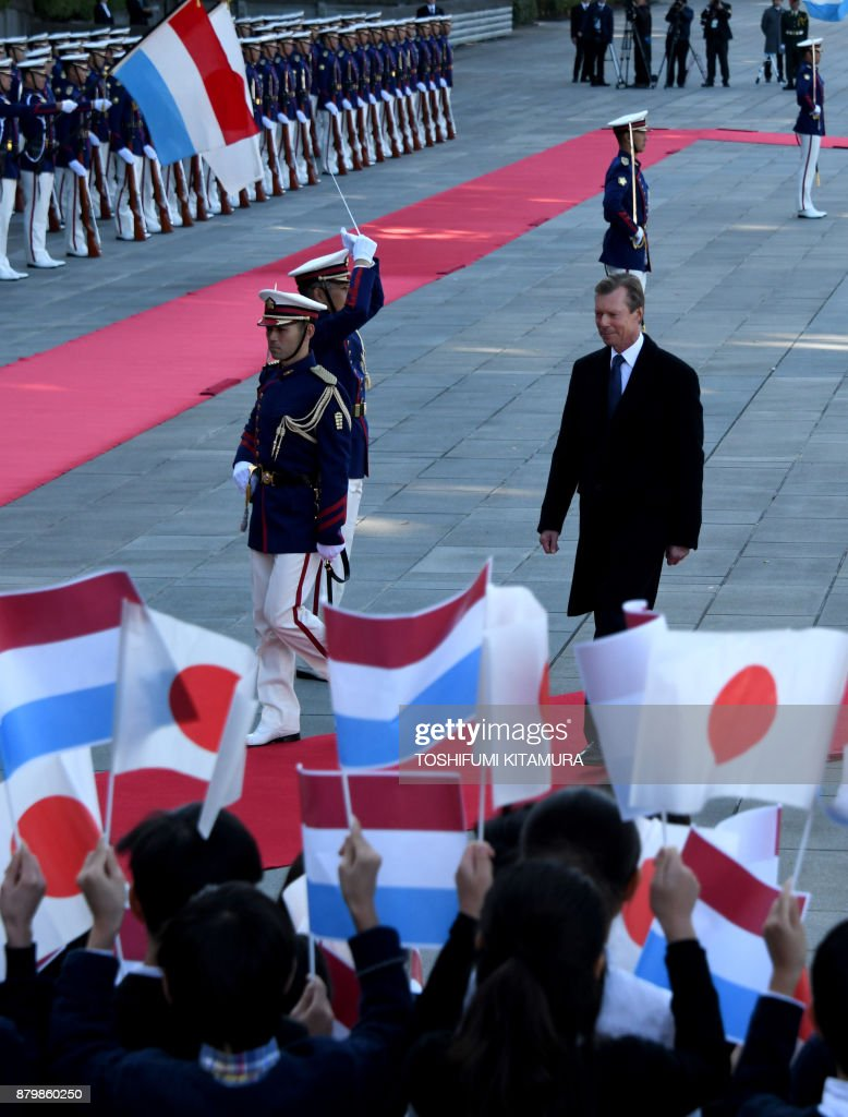 Luxembourg Grand Duke Henri (R) walks in front of students of an elementary school while reviewing a honor guard during his welcoming ceremony at the Imperial Palace in Tokyo on November 27, 2017. Grand Duke Henri and Princess Alexandra of Luxembourg are on a four-day visit to Japan. / AFP PHOTO / POOL / Toshifumi KITAMURA