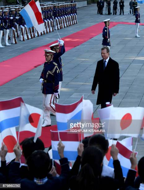 Luxembourg Grand Duke Henri walks in front of students of an elementary school while reviewing a honor guard during his welcoming ceremony at the...