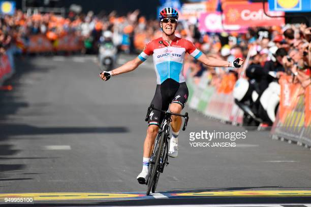 Luxembourg's Bob Jungels of the QuickStep Floors team celebrates as he crosses the finish line to win the 104th edition of the LiegeBastogneLiege one...